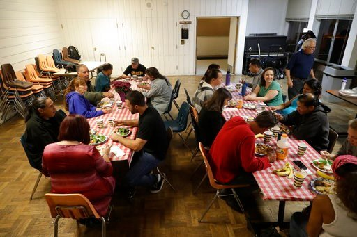 In this photo taken Oct. 10, 2017, group of homeless people, including Ellen Tara James-Penney (wearing blue) left, a lecturer at San Jose State University, receive a meal at Grace Baptist Church in San Jose, Calif.  (AP Photo/Marcio Jose Sanchez)