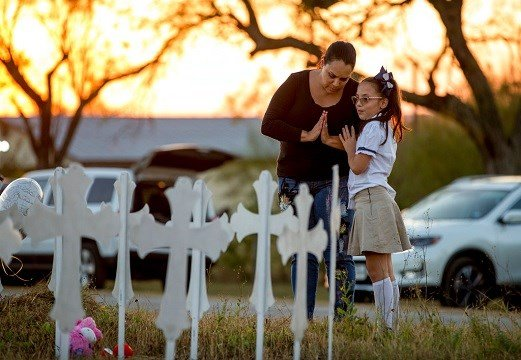 Meredith Cooper, of San Antonio, Texas, and her 8-year-old daughter, Heather, visit a memorial of 26 metal crosses near First Baptist Church.