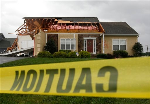 Caution tape hangs in front of a house that was heavily damaged by a possible tornado in Lewes, Del., Sunday, Aug. 28, 2011, after Hurricane Irene churned along the Delaware coast overnight.