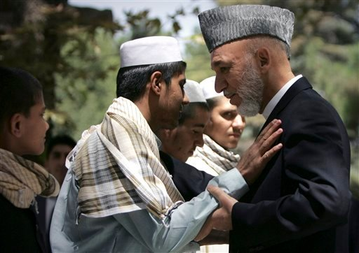 Afghan President Hamid Karzai, right, greets a youth suicide bomber during a meeting with at the presidential palace in Kabul, Afghanistan Wednesday, Aug. 24, 2011.