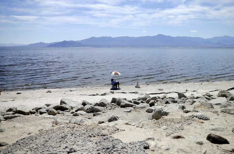 In this April 30, 2015 file photo, Ed Victoria of Los Angeles sits under an umbrella as he fishes for tilapia along the receding banks of the Salton Sea near Bombay Beach, Calif.
