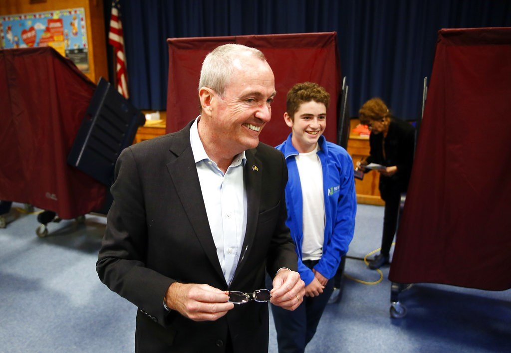 Democrat Phil Murphy exits the polling booth with his youngest son Sam, after voting at the Fairview School on Tuesday, Nov. 7, 2017 in Middletown, N.J. (Bob Karp/The Daily Record via AP)