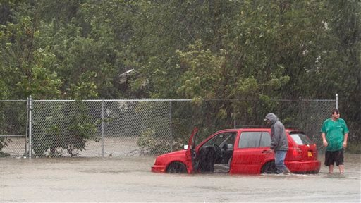 People try to get a car out of a flooded parking lot in Washingtonville, N.Y., Sunday Aug. 28, 2011.  (AP Photo/Paul Kazdan)