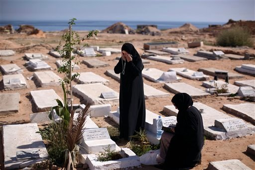 Jeria Birn Ismail, left, prays at the grave of rebel fighters who were killed in Tripoli fighting against Moammar Gadhafi's troops, on the first day of Eid al-Fitr in Tripoli, Libya, Wednesday, Aug. 31, 2011. (AP Photo/Alexandre Meneghini)