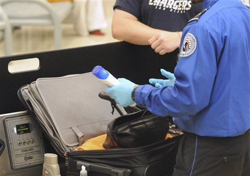 FILE In this Aug. 3, 2011 file photo, a Transportation Security Administration (TSA) checks passenger's carry on luggage at the security checkpoint at Hartsfield-Jackson Atlanta International Airport in Atlanta.