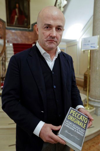"""Journalist Gianluigi Nuzzi holds a copy of his latest book """"Peccato Originale"""" (Original Sin) as he poses for photos during a press conference to present it, in Rome, Thursday, Nov. 9, 2017."""