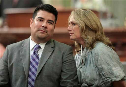 Assemblyman Ricardo Lara, D-Bell Gardens, talks with Assemblywoman Betsy Butler, D-Marina del Rey, as members of the state Assembly debate his measure that would allow students who are illegal immigrants to hold student government office.