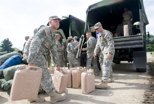 Kenneth Geib, left, and other members of the Army National Guard's 42nd Infantry Division work to load water, food and other supplies into trucks that will be taken to relief shelters Aug. 31, 2011. (AP Photo/The Daily Star, Benjamin Patton)