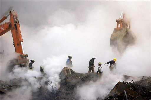 FILE - In this Oct. 11, 2001 file photo, firefighters make their way over the ruins of the World Trade Center through clouds of smoke at ground zero in New York.