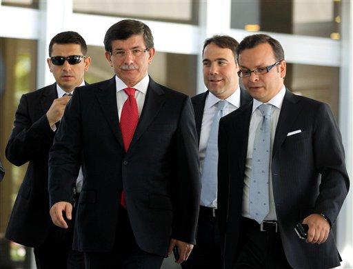 Turkish Foreign Minister Ahmet Davutoglu, centre left, leads advisors as he arrives to speak to the media in Ankara, Turkey, Friday, Sept. 2, 2011. (AP)