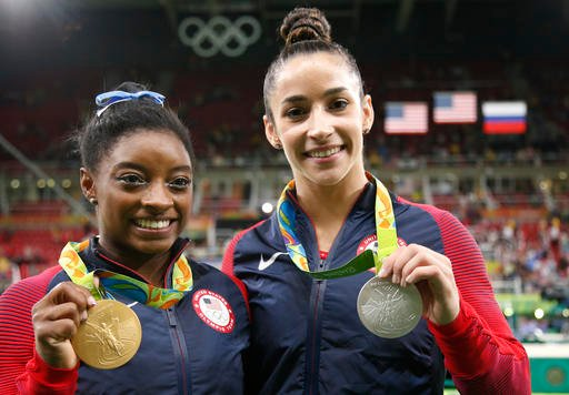 United States' Simone Biles, left, and compatriot Aly Raisman display their gold and silver medals respectively during the medal ceremony for the artistic gymnastics women's individual all-around at the 2016 Summer Olympics in Rio de Janeiro, Brazil.