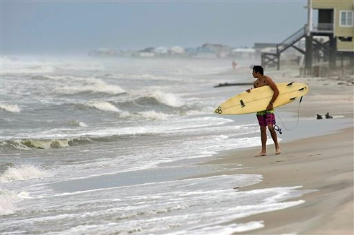 A surfer waits with his board to surf Thursday, Sept. 1, 2011, in Dauphin Island, Ala. Forecasters have issued tropical storm warnings for the U.S. Gulf coast from Mississippi to Texas as a depression has organized in the Gulf of Mexico. (AP)