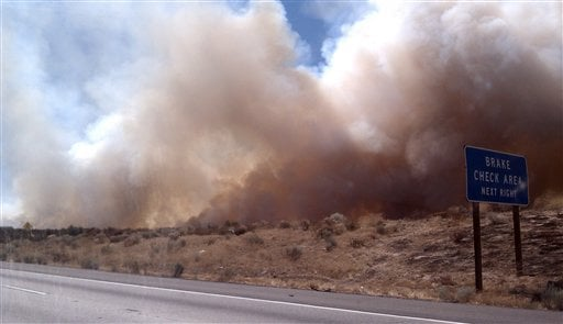 This image provided by Cindy Kent shows a wildfire burning alongside Interstate 15, Friday Sept. 2, 2011 in the high desert northeast of Los Angeles.