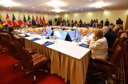 The empty seat, foreground, for Canada's Prime Minister Justin Trudeau, is seen during a meeting of the Trans-Pacific Partnership (TPP) on the sidelines of the Asia-Pacific Economic Cooperation (APEC) summit in Danang, Vietnam, Friday, Friday, Nov. 10, 20