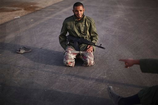 Rebel fighter Ani Saklen, 25, a mobile phone vendor, chats with a colleague at a checkpoint between Tarhouna and Bani Walid, Libya, Monday, Sept. 5, 2011. (AP Photo/Alexandre Meneghini)