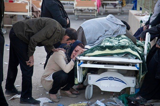 In this photo provided by Tasnim News Agency, relatives weep over the body of an earthquake victim, in Sarpol-e-Zahab, western Iran.