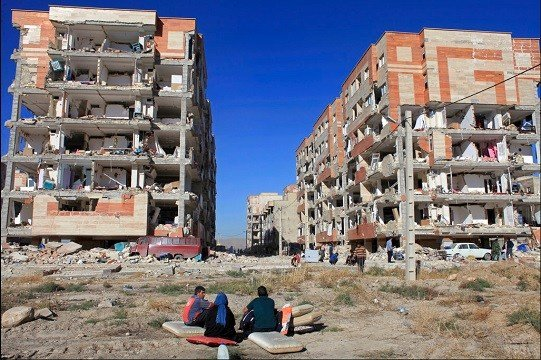 Survivors sit in front of buildings damaged by an earthquake, in Sarpol-e-Zahab, western Iran.