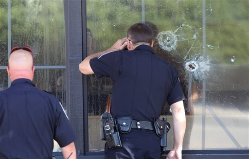 Officers look through a bullet-damaged window of an IHOP restaurant in Carson City, Nev. on Tuesday, Sept. 6, 2011. Seven people were wounded after a gunman opened fire at the restaurant, authorities said. (AP Photo/Cathleen Allison)