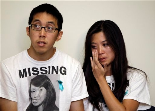 Michael Le, left, brother of Michelle Le, and Krystine Dinh, right, cousin of Michelle Le, listen during a news conference at the Hayward Police Department in Hayward, Calif., Wednesday, Sept. 7, 2011.