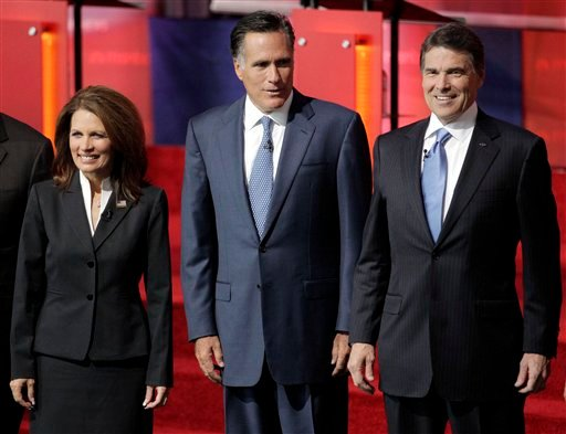 Republican presidential candidates, from left, Rep. Michele Bachmann, R-Minn., former Massachusetts Gov. Mitt Romney, and Texas Gov. Rick Perry, stand together before a Republican presidential candidate debate at the Reagan Library.