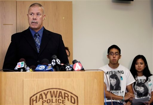 Michael Le, left, brother of Michelle Le, and Krystine Dinh, right, cousin of Le, listen during a news conference at the Hayward Police Department as they listen to Lt. Roger Keener speak, in Hayward, Calif., Wednesday, Sept. 7, 2011.