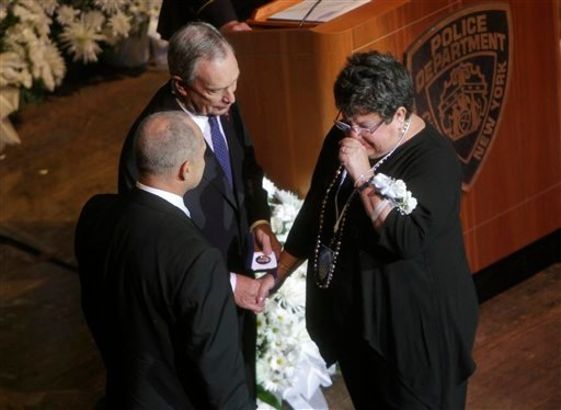 Harriet Epstein becomes emotional as she accepts a commemorative medallion from New York City Mayor Michael Bloomberg, center, and Police Commissioner Raymond Kelly during a ceremony to honor police officers killed during or as a result of 9/11.