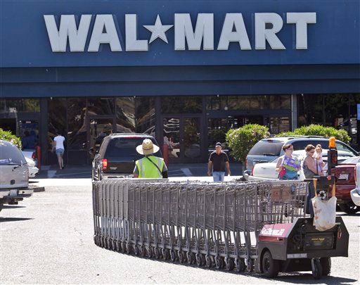 In this June 20, 2011 photo, a Wal-Mart worker pulls carts at a Wal-Mart store in Pittsburg, Calif.