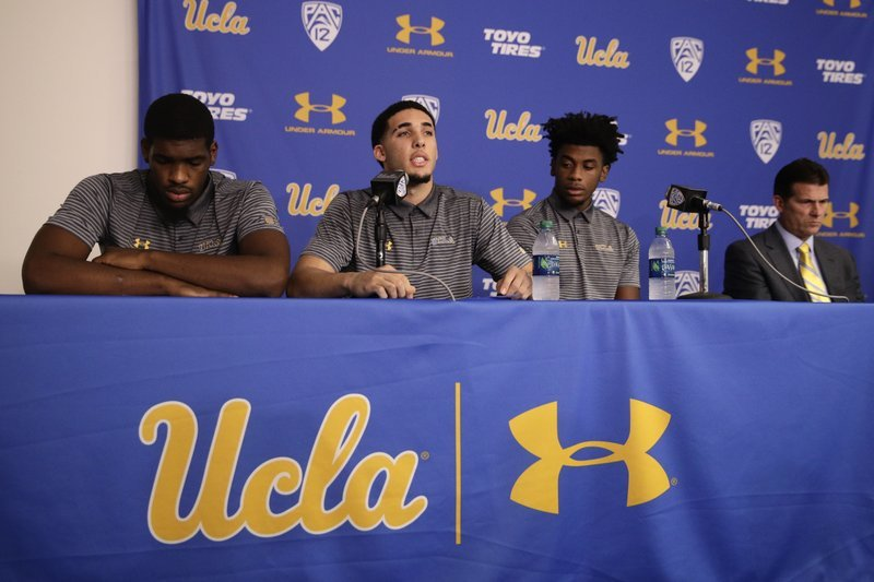 Flanked by Cody Riley, left, and Jalen Hill, third from left, UCLA basketball player LiAngelo Ball reads his statement as head coach Steve Alford listens during a news conference at UCLA Wednesday, Nov. 15, 2017, in Los Angeles.