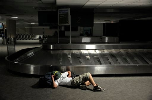 A stranded passenger sleeps in the baggage claim area at San Diego's Lindbergh Field after a blackout Thursday, Sept. 8, 2011. A power outage is affecting millions of people across southern California, Arizona and Mexico. (AP Photo/Denis Poroy)