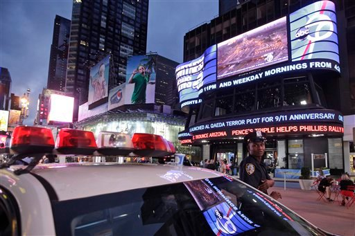A police officer stands guard in New York's Times Square as the ABC news ticker displays news of an al-Qaida terror threat, Friday, Sept. 9, 2011.