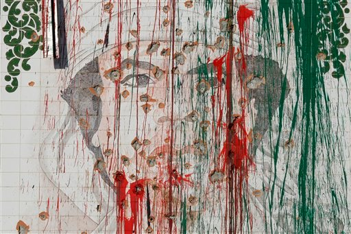 A portrait depicting Libya's former ruler Muammar Qaddafi is riddled with bullet marks and vandalized with paint on a wall in Tripoli, Libya, Thursday, Sept. 8, 2011.
