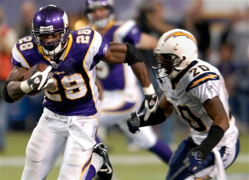 FILE - In this Nov. 4, 2007 file photo, Minnesota Vikings running back Adrian Peterson, left, runs past San Diego Chargers safety Marlon McCree, right, during the third quarter of an NFL football game in Minneapolis.