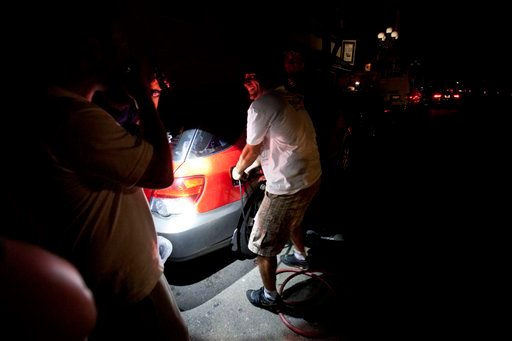 A man tries to syphon gas from a car during a power outage Thursday, Sept. 8, 2011, in San Diego. A power outage is affecting millions of people across southern California, Arizona and Mexico.