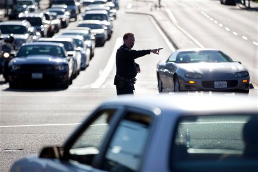 A San Diego police official directs traffic after a power outage Thursday, Sept. 8, 2011, in San Diego. A power outage is affecting millions of people across southern California, Arizona and Mexico.