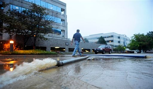 Pumps remove water from a parking garage in Alexandria after flooding filled the first floor of the garage with four-feet of water, Friday, Sept. 9, 2011. (AP Photo/Cliff Owen)
