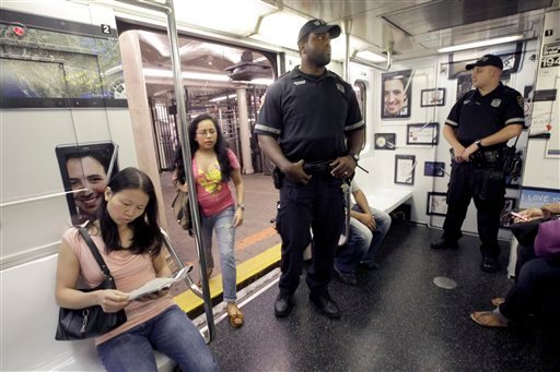 A couple of police officers ride the shuttle between New York's Times Square and Grand Central Station, Friday, Sept. 9, 2011.