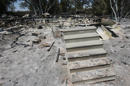 Stairs sit in front of a home destroyed by wildfires Friday Sept. 9, 2011 near Whitney, Texas. Over 500 acres of land burned including six homes.