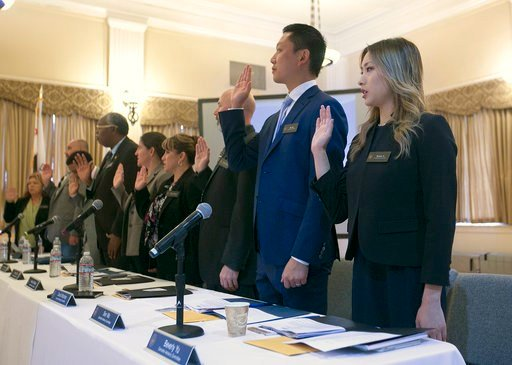 Beverly Yu, right, and other members of the Cannabis Advisory Committee, are sworn in during the committee's first meeting, Thursday, Nov. 16, 2017, in Sacramento, Calif. The committee released the rules governing the nation's largest legal recreation mar