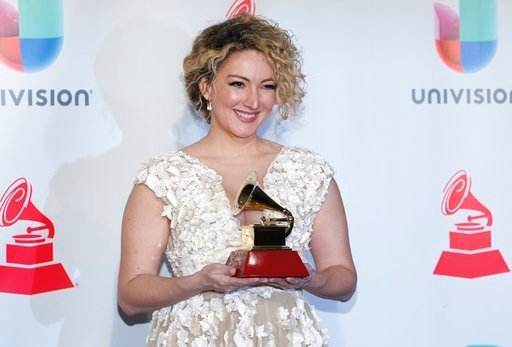 "Erika Ender poses in the press room with the award for song of the year for ""Despacito"" at the 18th annual Latin Grammy Awards at the MGM Grand Garden Arena on Thursday, Nov. 16, 2017, in Las Vegas. (Photo by Eric Jamison/Invision/AP)"