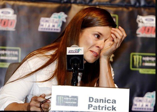 Danica Patrick wipes away tears as he speaks with the media during a news conference.