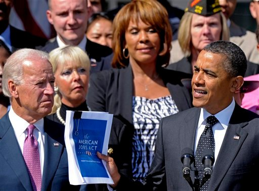 President Barack Obama, accompanied by Vice President Joe Biden, and others, holds up a copy of his American Jobs Act during a statement in the Rose Garden of the White House in Washington, Monday, Sept. 12, 2011.
