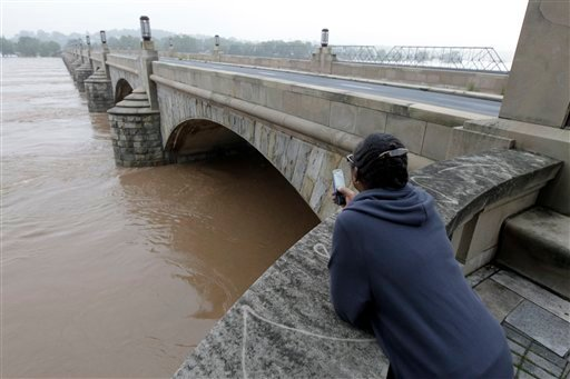 Lucy Mitchell looks at the high water level during flooding of the Susquehanna River caused by rainfall from the remnants of Tropical Storm Lee, as the water flows under the closed Market Street Bridge, Friday, Sept. 9, 2011, in Harrisburg, Pa.