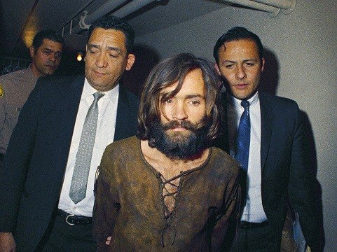 Charles Manson is escorted to his arraignment on conspiracy-murder charges in connection with the Sharon Tate murder case.