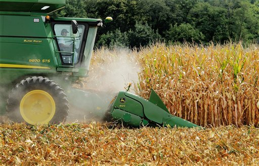 FILE - This file photo taken Aug. 30, 2011, in Central Illinois shows farmer Jason Podany using a combine to harvest corn near Farmingdale, Ill.