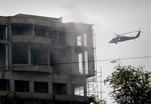 A military helicopter belonging to coalition forces flies around a building during a gun battle with Taliban militants in Kabul, Afghanistan on Wednesday Sept. 14,2011. (AP Photo/Musadeq Sadeq)