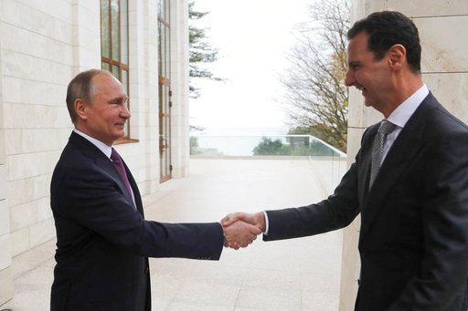 In this photo taken on Monday, Nov. 20, 2017, Russian President Vladimir Putin, left, shakes hand with Syrian President Bashar Assad in the Bocharov Ruchei residence in the Black Sea resort of Sochi, Russia, Tuesday, Nov. 21, 2017. (Mikhail Klimentyev, Kr
