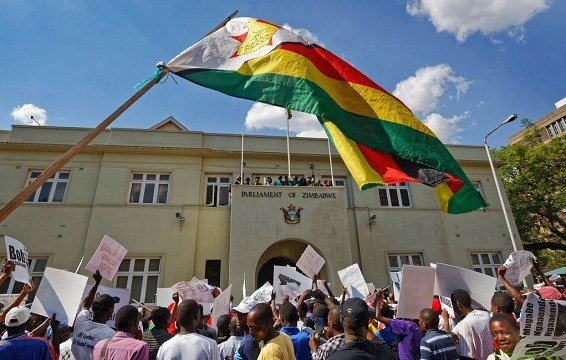 Protesters calling for the impeachment of President Robert Mugabe demonstrate outside the parliament building in downtown Harare, Zimbabwe.