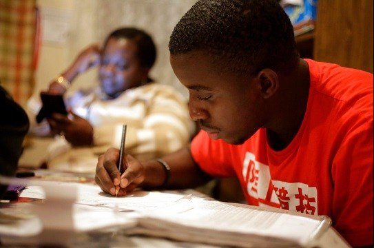 Amocachy Jeune, right, does homework as his mother Marianne Jeune, left, a Haitian immigrant staying in the U.S. through the Temporary Protected Status program.