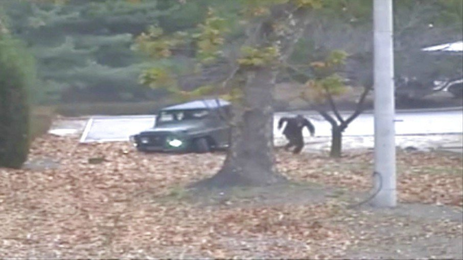 This image made from Nov. 13, 2017, surveillance video released by the United Nations command shows a North Korean soldier running from a jeep and later shot by North Korean soldiers. (United Nations Command via AP)