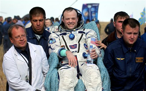 Russian Space Agency specialists carry NASA Astronaut Ron Garan after landing of the Russian Soyuz TMA-21 space capsule about 150 kilometers (94 miles) southeast of the Kazakh town of Zhezkazgan, Kazakhstan, on Friday, Sept. 16, 2011. (AP)